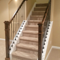 Open stairway with wood railing and newel post in Brothers finished basement
