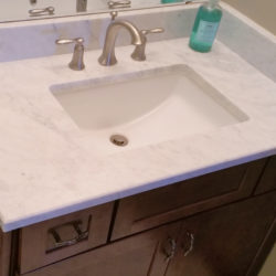 cherry vanity and wide spread lavatory faucet in 3/4 bath in walk-out basement