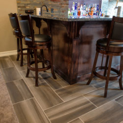 Detail of custom wet bar wood work with porcelain tile floor and granite counter in finished basement